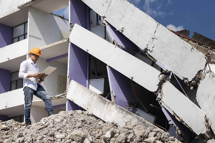 Natural Disaster Insurance - Engineer Looking Over the Rubble with an iPad in Hand