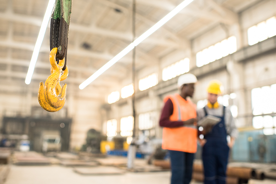 Specialized Business Insurance - Interior of Spacious Production Department of Modern Plant with Team of Machine Operators Discussing Manufacturing Process and Blurred in the Distance